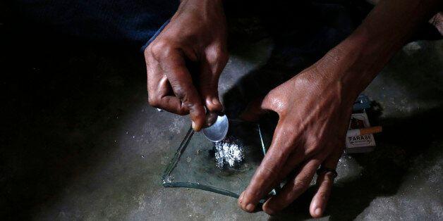 A heroin addict prepares heroin before using it in Lamu November 21, 2014. Picture taken November 21, 2014.   To match KENYA-