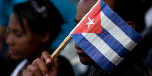 A Cuban fan uses a paper flag to shield his face from the sun during a baseball game between the Tampa Bay Rays and the Cuban