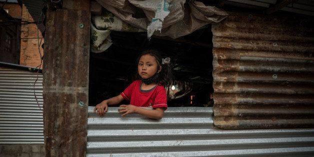KATHMANDU, BHAKTAPUR - APRIL 24:  A girl in an open window of a typical metal sheet temporary shelter in Bhaktapur on April 2