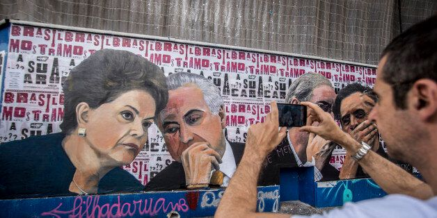 SAO PAULO, BRAZIL - APRIL 22:  People pass a mural depicting president of Brazil Dilma Rousseff and Vice President Michel Tem