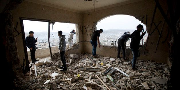Palestinians inspect the damaged house of Zaid Amer, after it was demolished by the Israeli army, in the West Bank city of Na