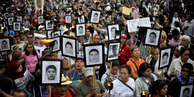 The parents of 43 missing students from Ayotzinapa teachers school hold their portraits and torches during a march 18 months
