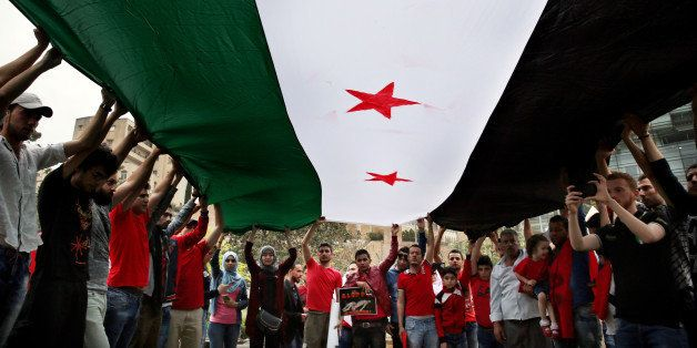 Protesters hold up a giant Syrian revolution flag during a protest in front of the United Nations Headquarters in Beirut, Leb