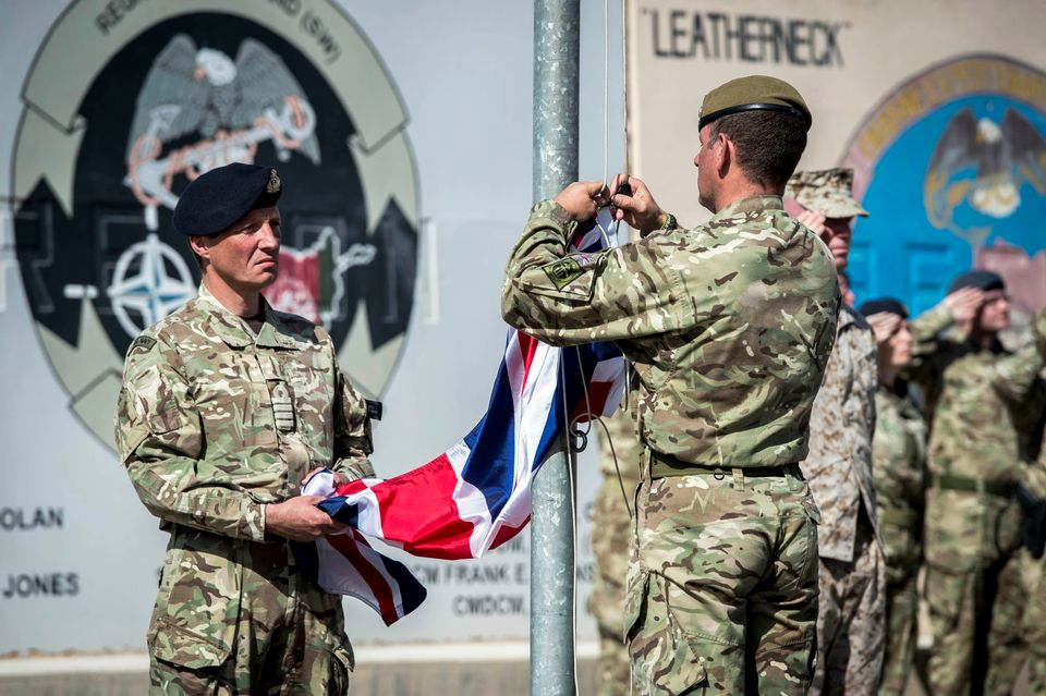 The last Union flag of Great Britain flying above the skies of Helmand Province, Afghanistan, is lowered by Captain Matthew C