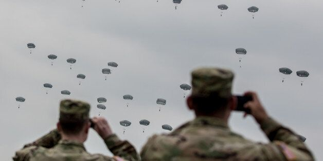 GRAFENWOEHR, GERMANY - APRIL 12:  U.S. soldiers look at paratroopers from the U.S. Army 173rd Airborne Brigade, the UK's 16 A