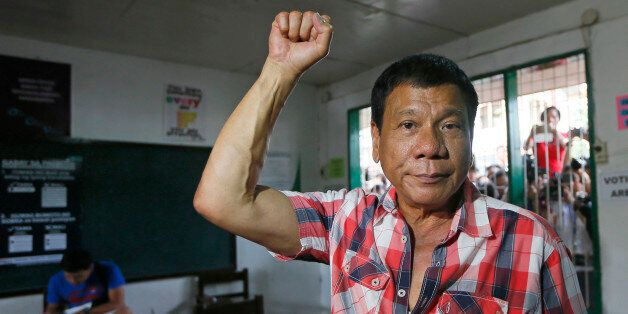 Front-running presidential candidate Mayor Rodrigo Duterte clenches his fist prior to voting in a polling precinct at Daniel