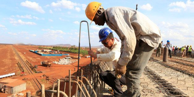 A Chinese engineer and a local construction worker work on a section of the Mombasa-Nairobi standard gauge railway (SGR) in E