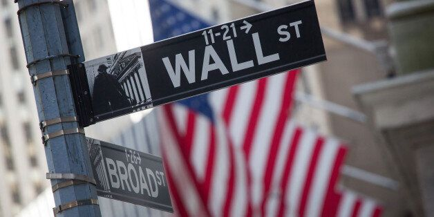 A Wall Street street sign is displayed in front of the New York Stock Exchange (NYSE) in New York, U.S., on Monday, April 18,