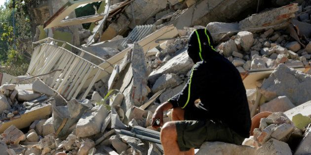 A man sits on the rubble of a collapsed building following an earthquake in Amatrice, central Italy,...