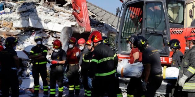 Rescuers carry away a body of a woman found in a collapsed house, in Amatrice, central Italy, Friday,...