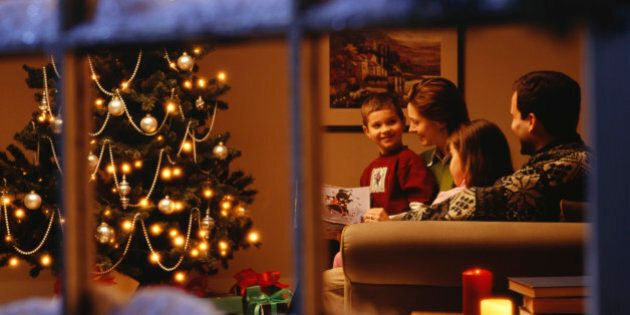 Family reading together on sofa at Christmas time, viewed through
