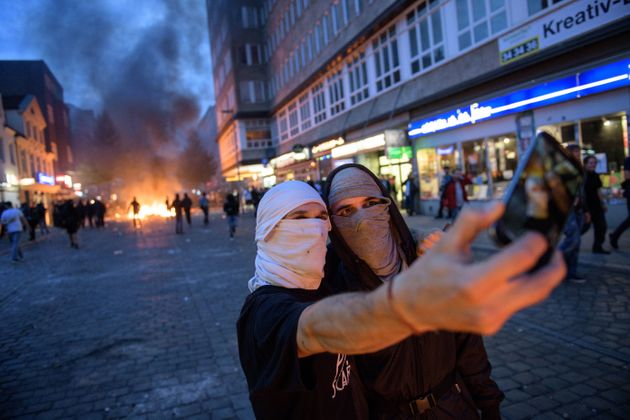 HAMBURG, GERMANY - JULY 07: Demonstrators take a selfie photo with a burning crush barrier in the background...