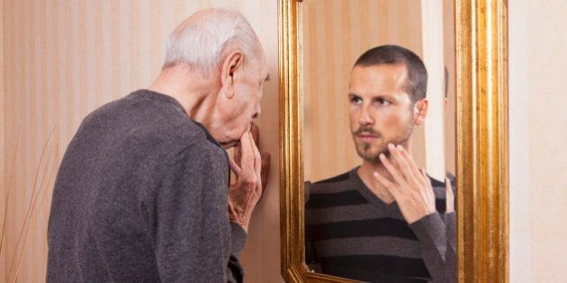 Elder man looking at an younger himself in the