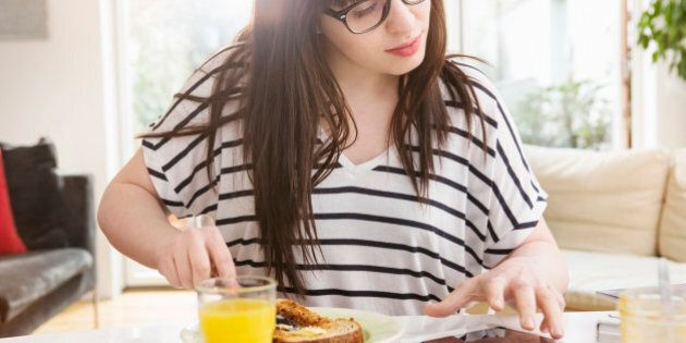 Woman at breakfast table checks digital