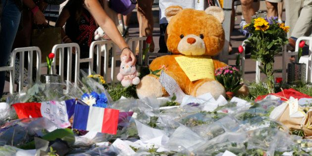 A woman places a stuffed toy alongside flowers, flags and a large stuffed toy in tribute to victims,...