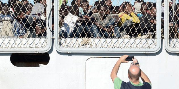 A police officer uses a mobile phone as migrants wait to disembark from the Italian Navy ship Borsini...