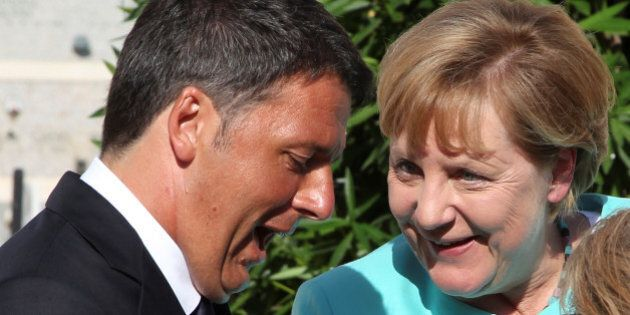 Italian Prime Minister Matteo Renzi (L) and German Chancellor Angela Merkel talk as they pay respect...