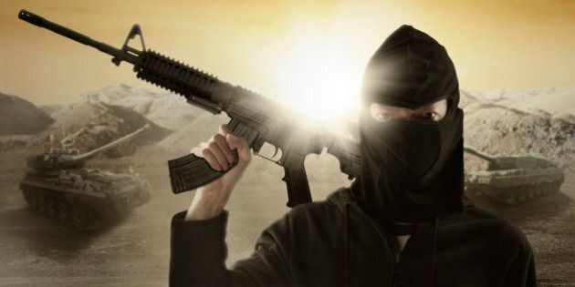 Male terrorist wearing mask and holding a machine gun with military vehicle