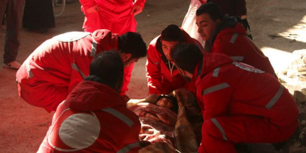 Members of the Syrian Arab Red Crescent help a sick woman in the rebel-controlled area of Aleppo's Bustan...