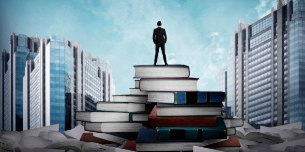Business man standing on the top of books looking the