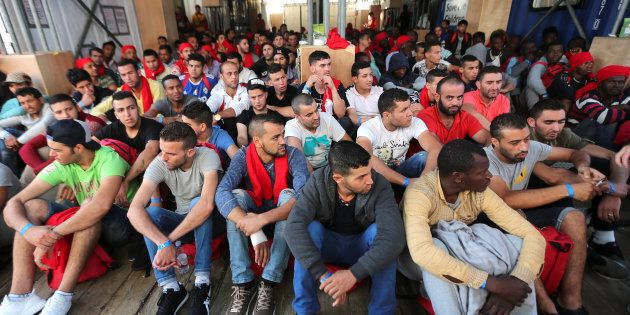 FILE PHOTO: Migrants waits to disembark from the Vos Hestia ship as they arrives in the Crotone harbour,...