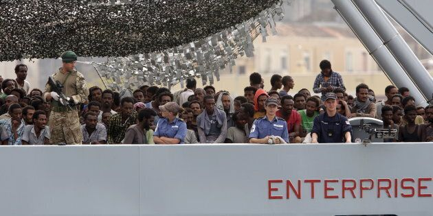 Migrants arrive on the British vessel HMS Enterprise before disembarking in the Sicilian harbour of Catania,...
