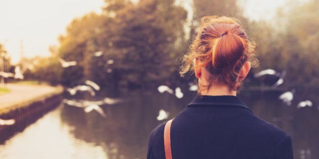 Rear view of a young redhead woman dressed in black looking at birds by a