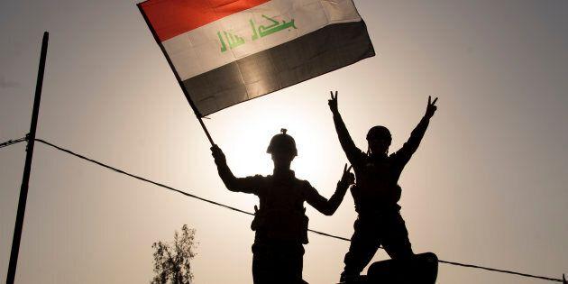 Due agenti della polizia federale irachena innalzano la bandiera nazionale per celebrare la liberazione...