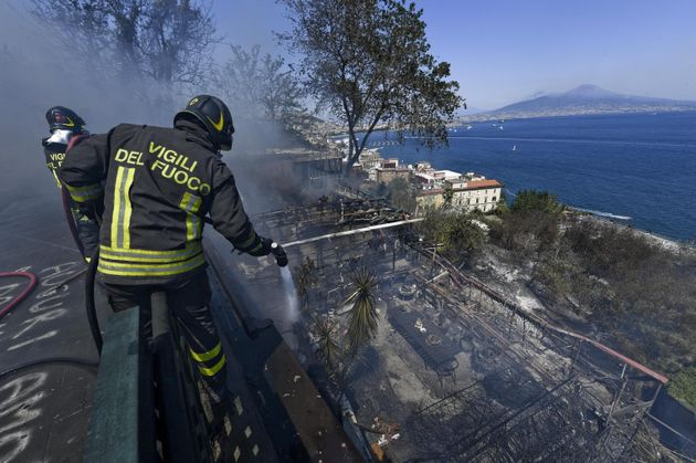 A firefighter works to extinguish the fire that broke out on the Posillipo hill, in the heart of Naples,...