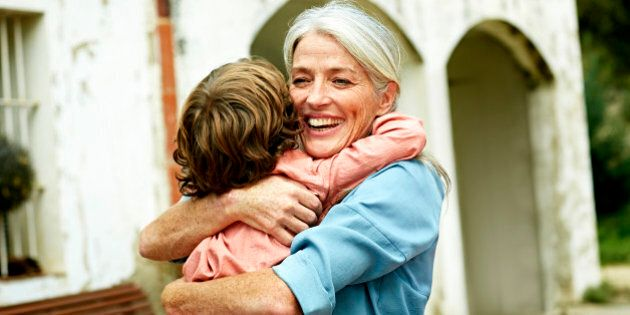Happy grandmother looking away while embracing grandson in