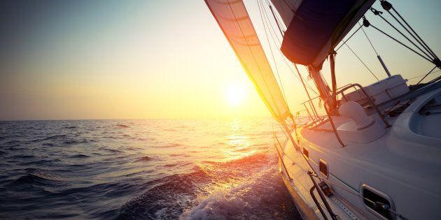 Sail boat gliding in open sea at