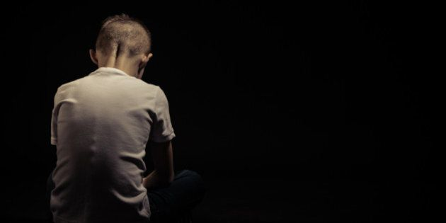 Rear View of a Sad Silhouette Young Boy Sitting on the Floor Against Black Background with Copy