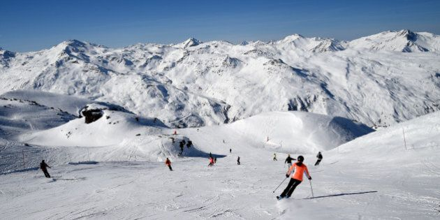 People ski in the French Alps ski resort of Les Menuires on February 16, 2017 during France's school...