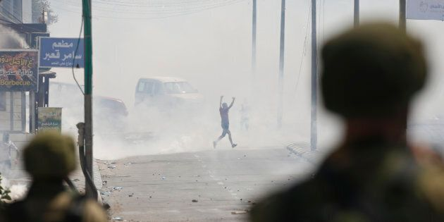 A Palestinian runs for cover from tear gas shot by Israeli soldiers during clashes in the West Bank city...