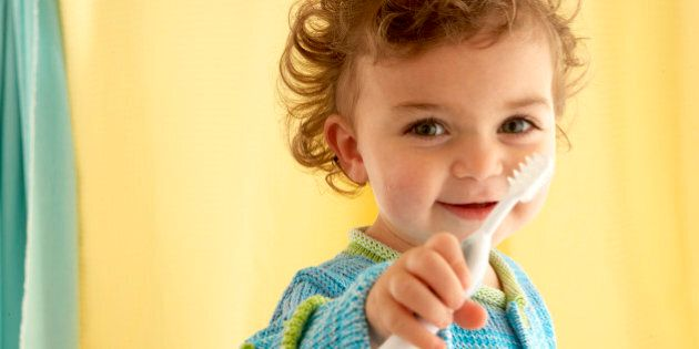Girl (21-24 months) holding toothbrush,