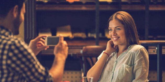 Young happy woman enjoying in a cafe while her boyfriend is photographing her with cell