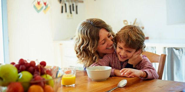 Happy mother embracing son while having breakfast at table in