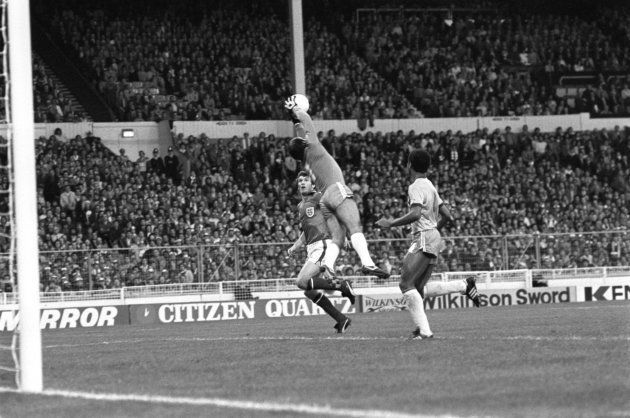 Brazil goalkeeper Valdir Peres (c) leaps to catch a cross as England's Peter Withe (l) waits for any