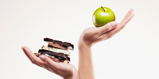 Woman cupping green apple above chocolate