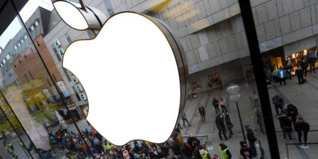 FILE - In this Friday, Sept. 25, 2015, file photo, people wait in front of an Apple store in Munich,...