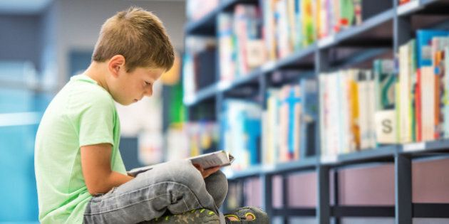 Schoolboy sitting on floor with book in
