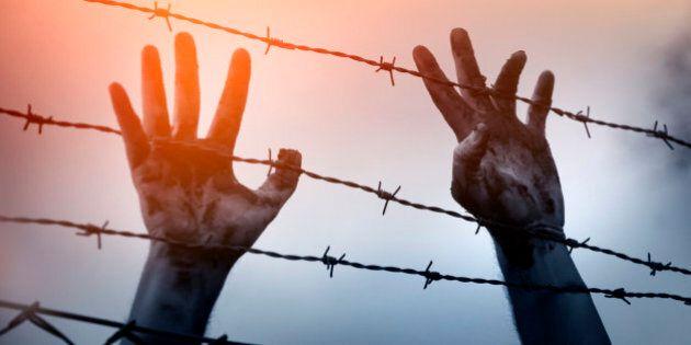 Refugee men and fence. Refugee