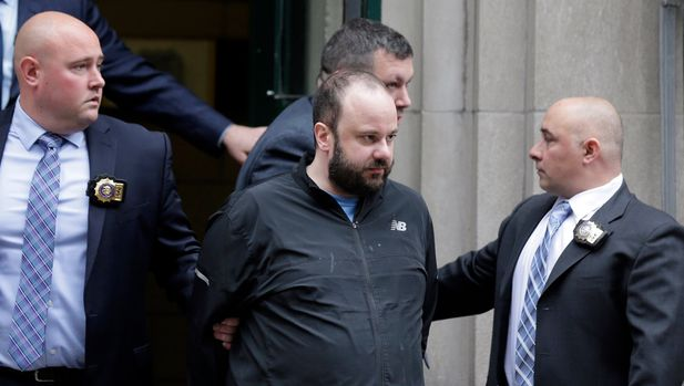 FILE - In this April 18, 2019, file photo, Marc Lamparello, 37, center, is escorted out of a police precinct in New York. Police say Lamparello was arrested after entering St. Patrick's Cathedral last week in New York with two cans of gasoline, lighter fluid and butane lighters. Lamparello made his initial court appearance, Wednesday, from a hospital. The judge ordered him to undergo a psychiatric evaluation. (AP Photo/Seth Wenig)