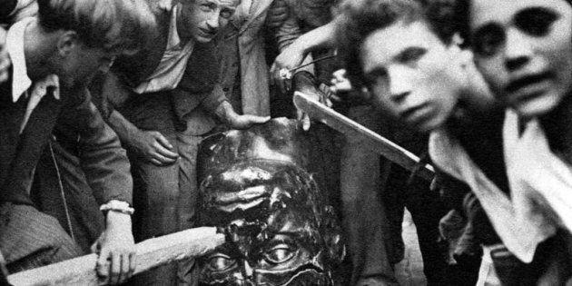 25 luglio 1943, Roma. Alla notizia della caduta del fascismo, un gruppo di persone depone la una statua...