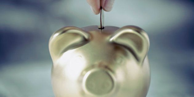 Person's hand putting coin into a piggy