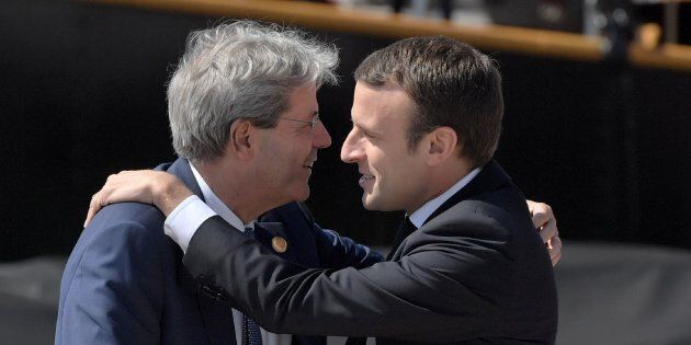 Italy's Prime Minister Paolo Gentiloni (L) embraces French President Emmanuel Macron upon his arrival...