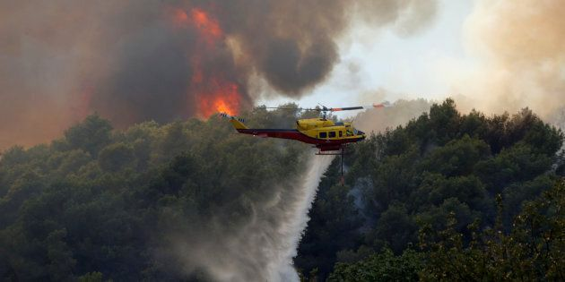 A helicopter drops water as flames and smoke from a burning wildfire fills the sky in Carros, near Nice,...
