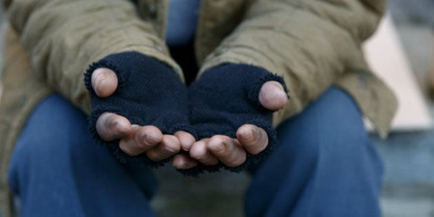 Man in need. Unhappy homeless man is holding hands to get