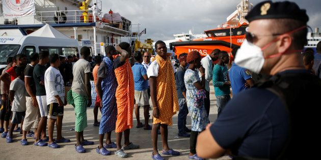 Migrants disembark from the vessel Topaz Responder as they arrive in the Sicilian harbour of Augusta,...