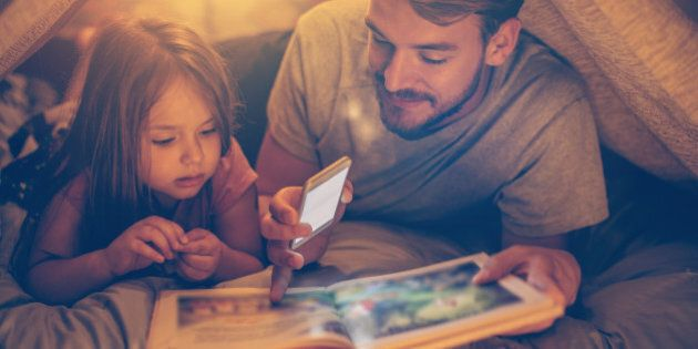 Father and daughter enjoying at home. Lying on bed at night in do it yourself tent and reading book together,...
